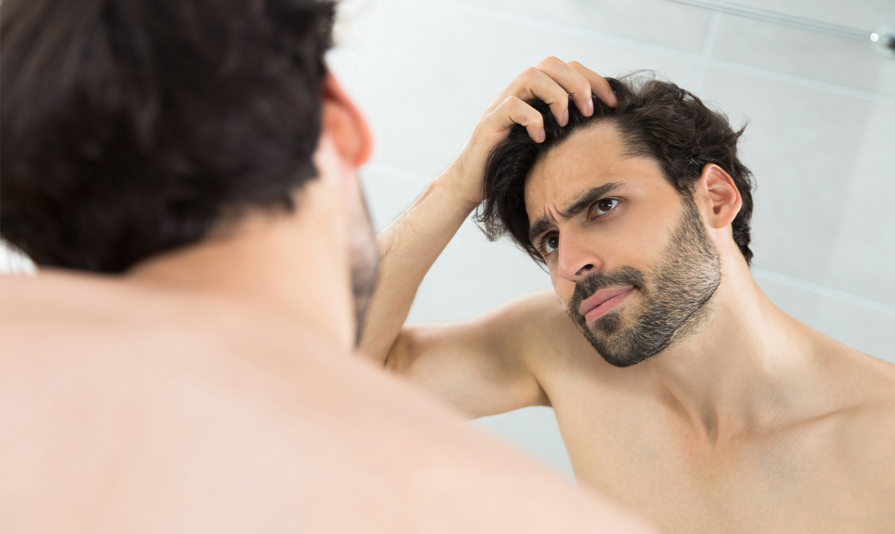 Male checking hair in mirror